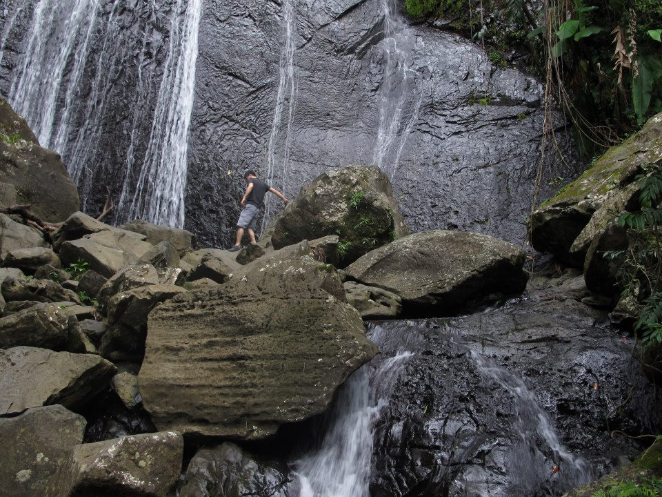 The contest winner climbing rocks under a waterfall at El Yunque National Forest, Puerto Rico