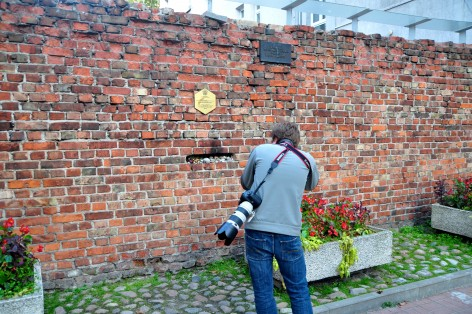 A visitor photographing a remaining wall of the Warsaw Ghetto