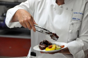 United Executive Chef Robin Carr applies a finishing touch to a meal